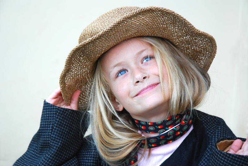 Beautiful little girl with hat. Head portrait of a cute little day dreaming Caucasian girl child dressed up with straw head, neck-tie and jacket looking up to stock photo