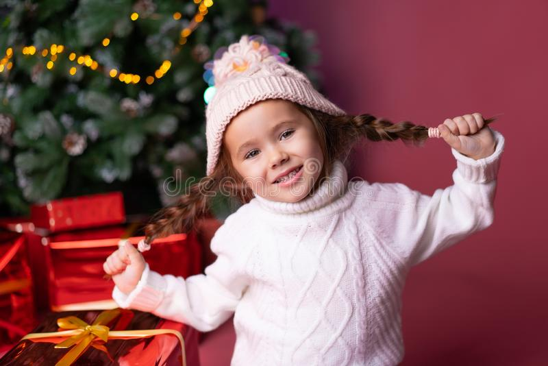 Beautiful little girl in the hat sitting near presents and christmas tree. Bokeh lights on the background. Concept. Christmas and new year stock photo