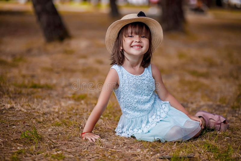 Beautiful little girl in a hat and white dress girl sitting on the lawn and laughing on a beautiful autumn warm day. stock photo