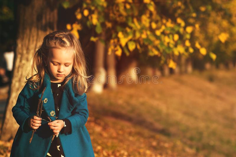 Beautiful little girl having fun in autumn park. Happy child outdoors. Autumn kids fashion. Autumn holidays. Copy space. Adorable stock photo