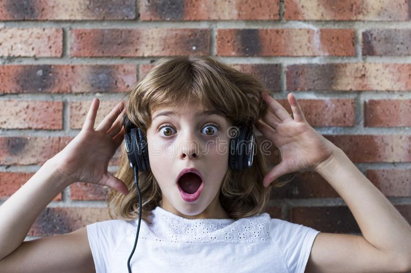 beautiful little girl with headphones at home listening to music and having fun, technology and music concept. Brick background stock image