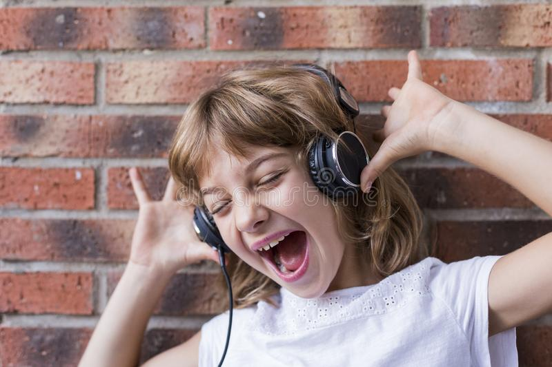 beautiful little girl with headphones at home listening to music and singing, technology and music concept. Brick background. royalty free stock image