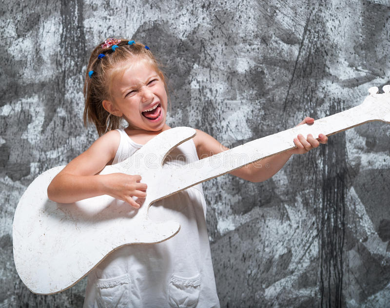 Beautiful little girl with her guitar stock photos