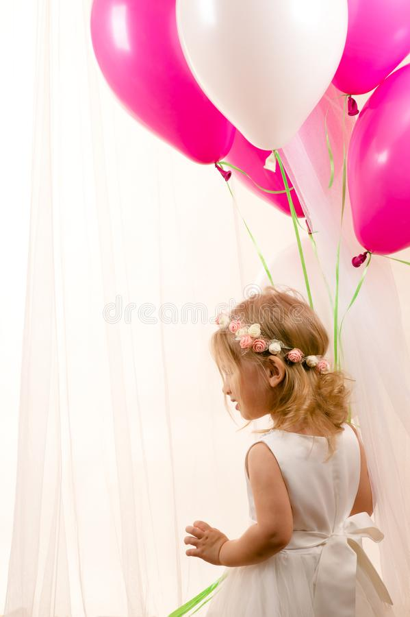 Beautiful little girl holding balloons at birthday party stock photos
