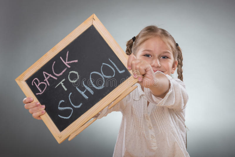 Beautiful little girl holding board on Back To School subtitles stock photos