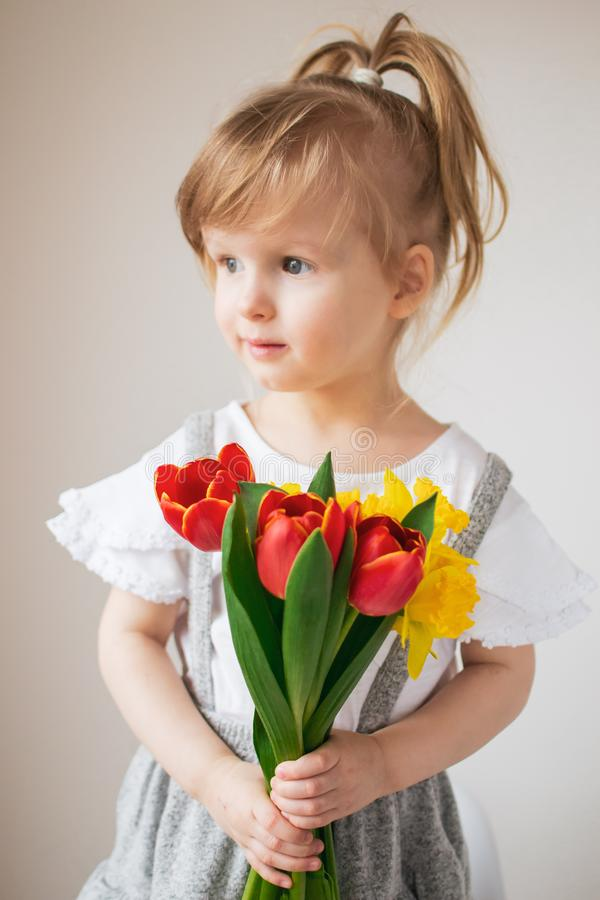 Beautiful little girl holding a bouquet of flowers stock image