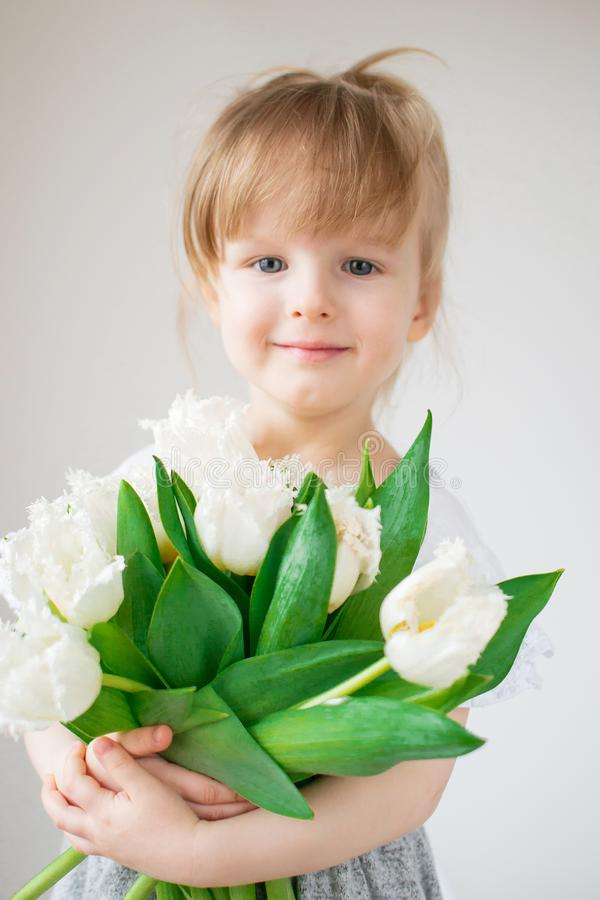 Beautiful little girl holding a bouquet of flowers. Mother`s day stock photography