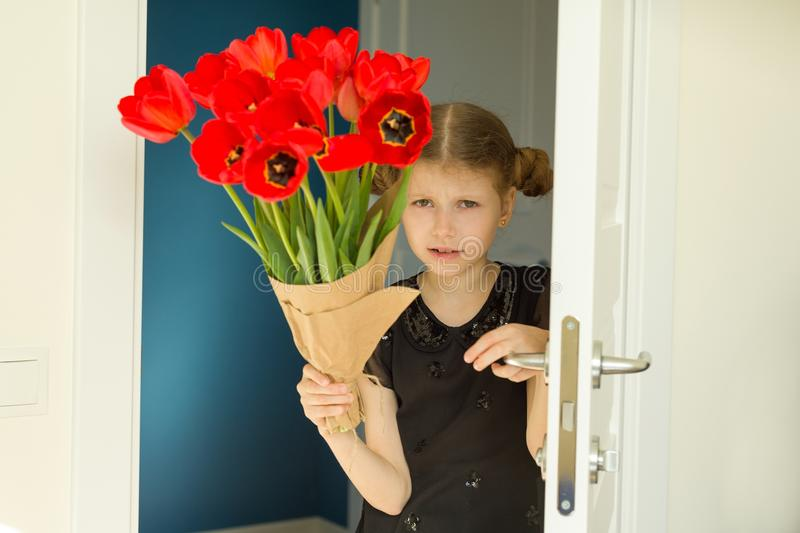 Beautiful little girl holding bouquet of flowers stock photo