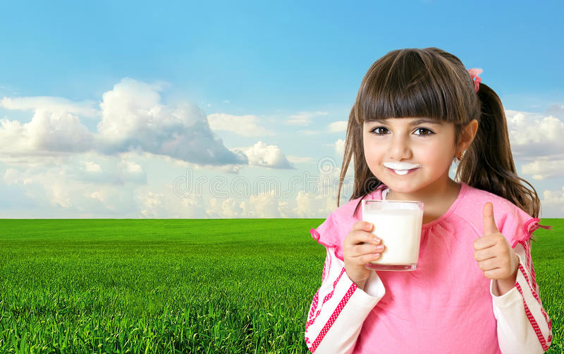 Beautiful girl holding a glass of milk in the background of green field and blue sky. Beautiful little girl holding a glass of milk and smiling in the background royalty free stock photography