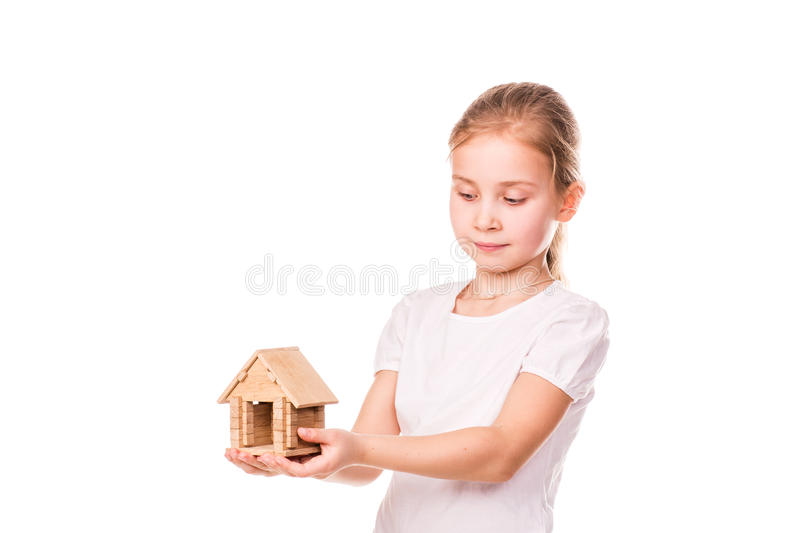 Beautiful little girl holding a toy model house. Buying a house concept. Beautiful little girl holding a toy model house isolated on white. Buying a house stock photos