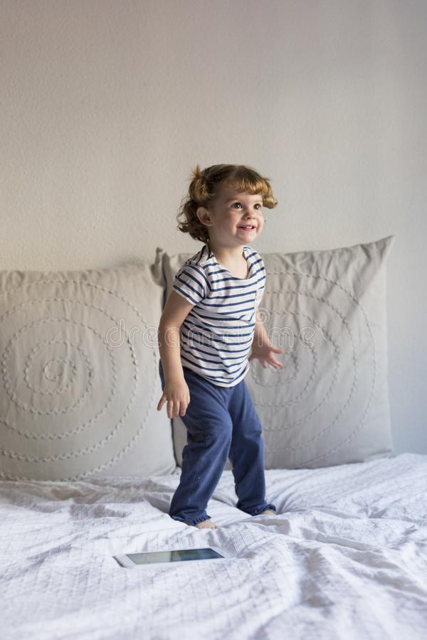 beautiful little girl jumping on bed and smiling. Fun, home, indoors. Lifestyle stock images