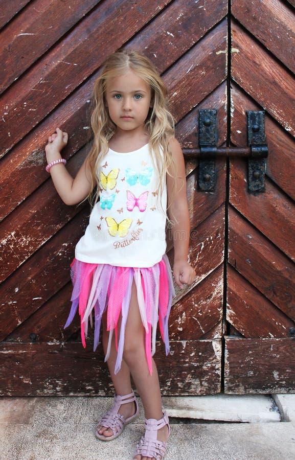 Beautiful little girl knocks on the door. Beautiful little girl knocks on the big old wooden door stock photos