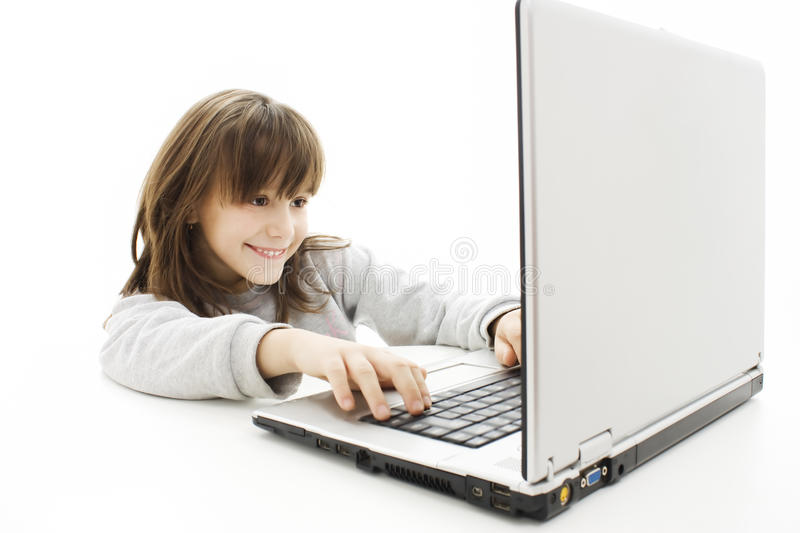 Beautiful little girl with laptop computer. royalty free stock image