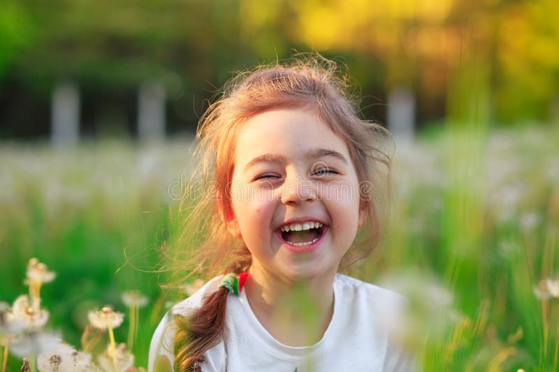 Beautiful little girl  laughing and playing with flowers in sunny spring park. Happy cute kid having fun outdoors at sunset royalty free stock photo