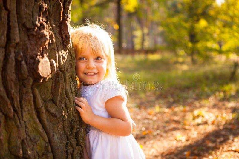Beautiful little girl leaning against big tree and smiling royalty free stock image