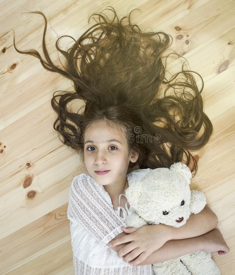 Beautiful little girl lies on a wooden floor with teddy bear royalty free stock photo