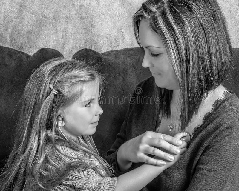 Beautiful little girl listening to her moms heart with a stethoscope B&W stock images