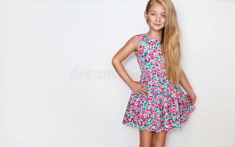 Beautiful little girl with long blond hair and blue eyes standing on a white background stock photos