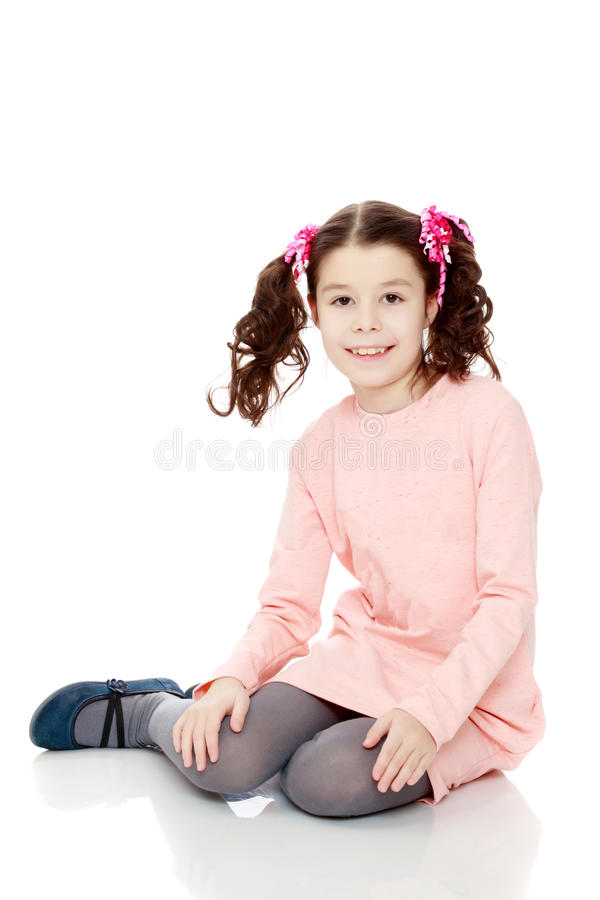 Little girl sitting on the floor and straightens hair. stock image