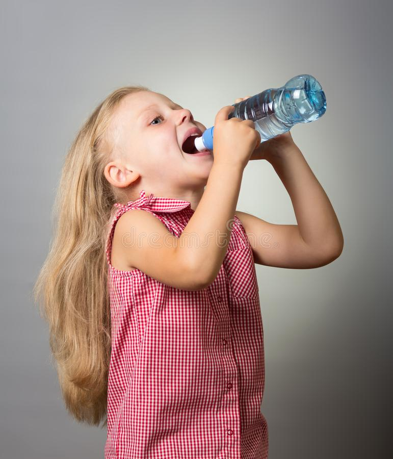 Beautiful little girl with long hair drinking water from bottle on gray royalty free stock image