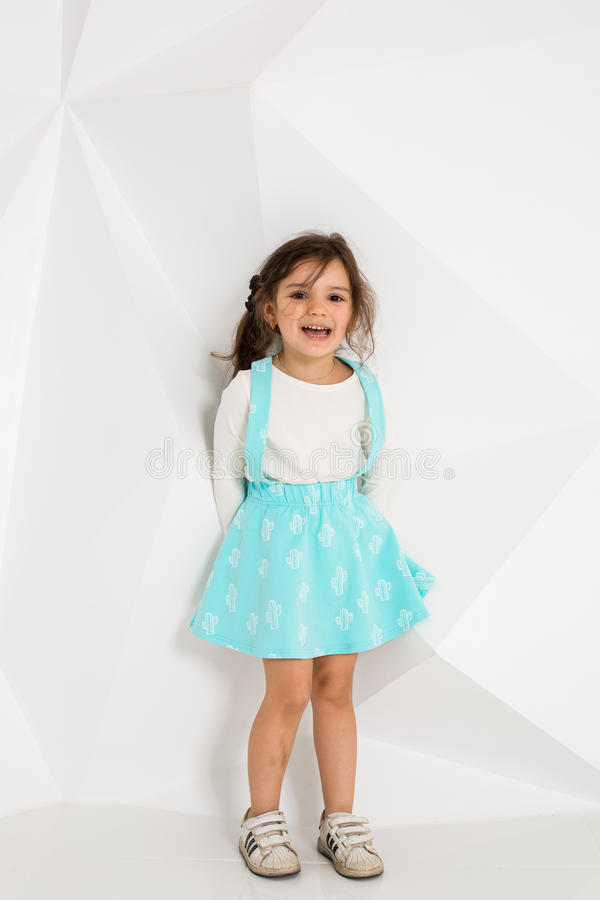 Beautiful little girl with long hair. In a lush short turquoise skirt and white T-shirt. stock photo