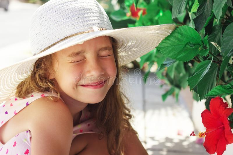 Beautiful little Girl looking at red flower and smiling in summer park. Happy cute kid playing outdoors stock photos
