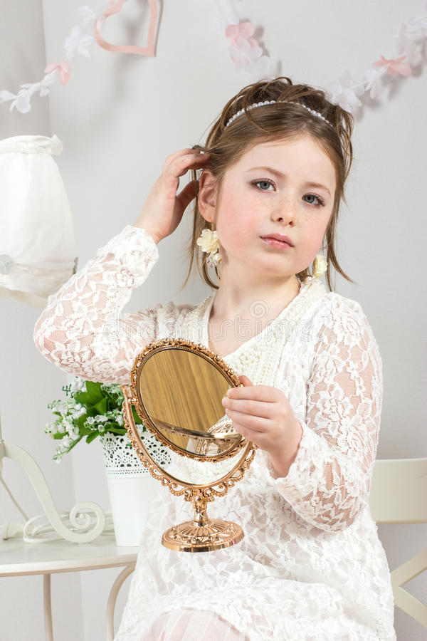 Download A Beautiful Little Girl Looking To Small Mirror Royalty Free Stock Photos - Image: 24130518
