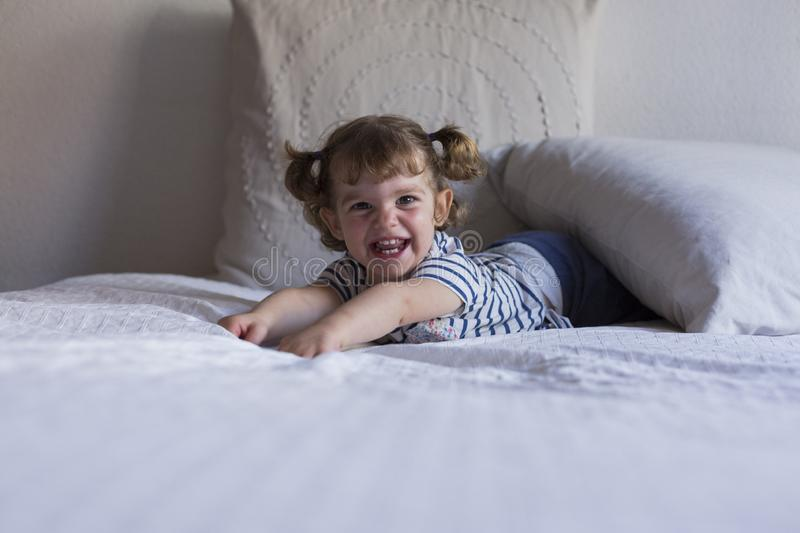 beautiful little girl lying on bed and smiling. Fun, home, indoors stock photography