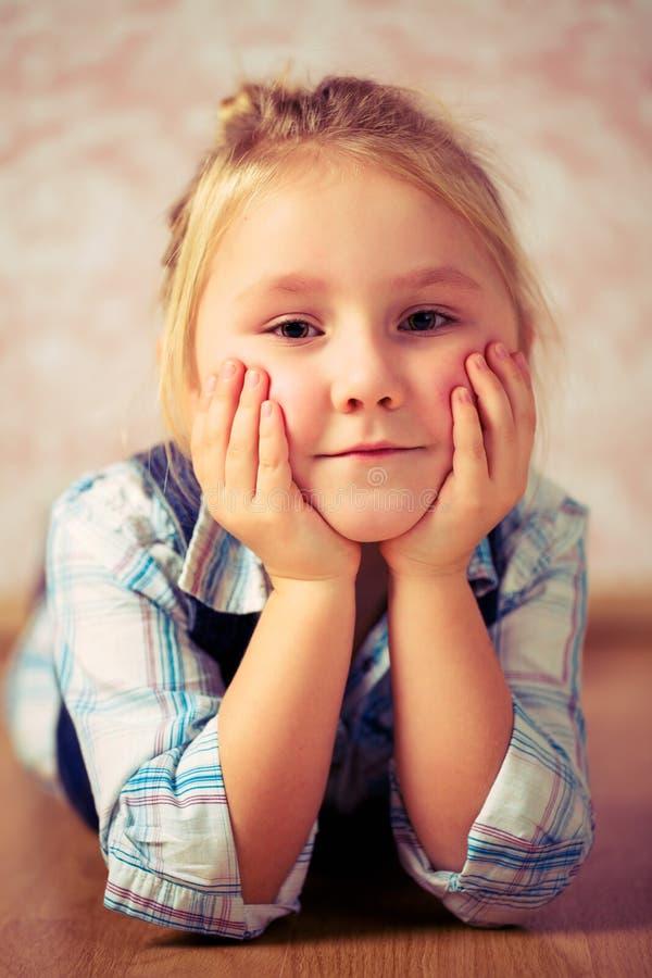 Beautiful little girl lying on floor royalty free stock image