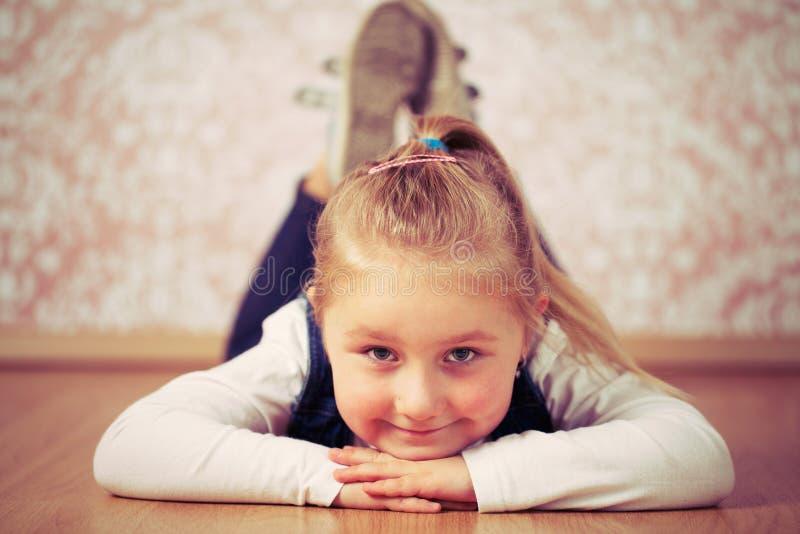 Beautiful little girl lying on floor royalty free stock images