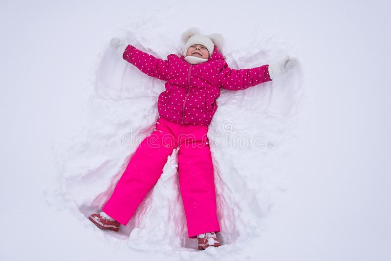 Beautiful little girl makes a snow angel in a park, top view. stock photography