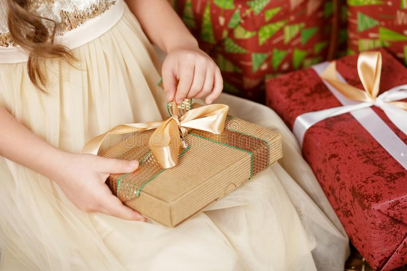 Beautiful little girl opening a Christmas gift box. Christmas and New Year celebration concept. Winter holidays. Close up picture royalty free stock image