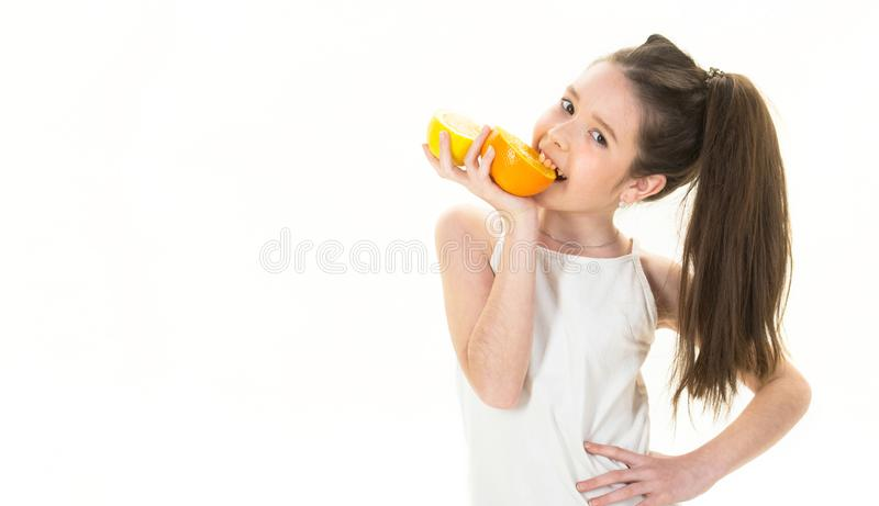 Beautiful little girl with oranges, lemons, grapefruits, vitamin. Baby girl holding a big juicy orange. Little girl stock image