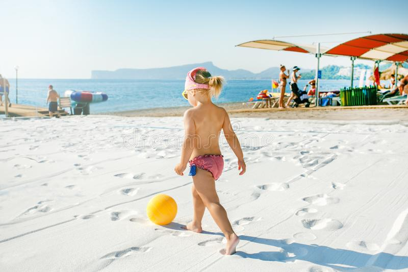 Child playing with ball on the beach. Summer vacation, family vacation concept stock photography