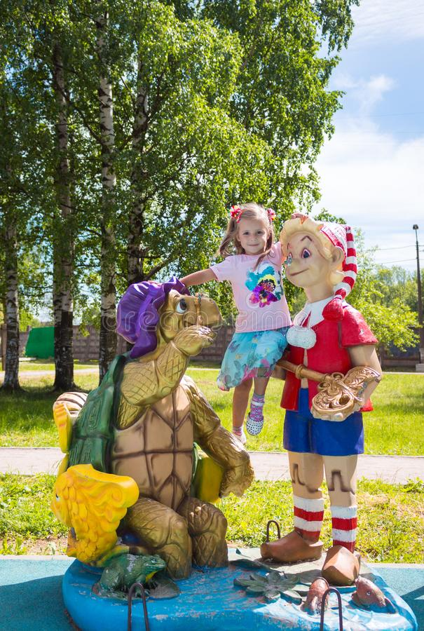 Beautiful little girl on the playground with Pinocchio and a turtle royalty free stock photos