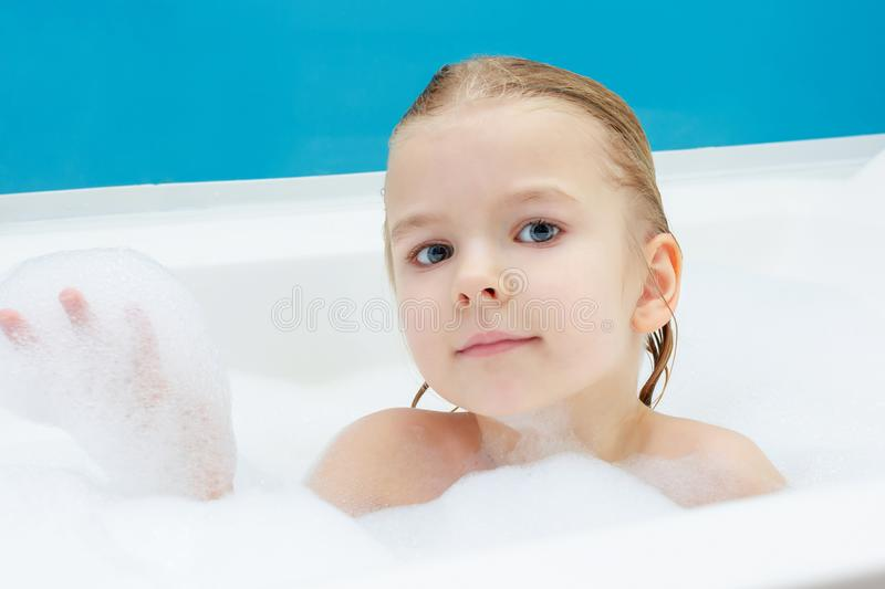 Beautiful, little girl playing in the bath with foam. Cute smiling baby. stock photos