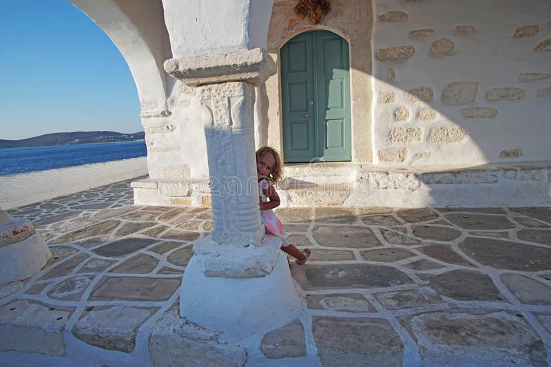 Beautiful little girl playing in the courtyard of the church of Agios Konstantinou, a traditional Cycladic church with a blue dome stock photos