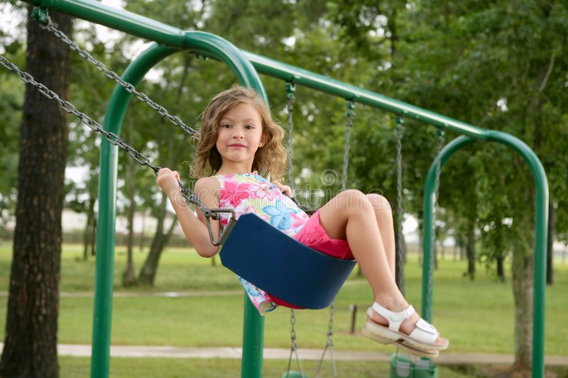 Beautiful little girl playing with swing stock photos