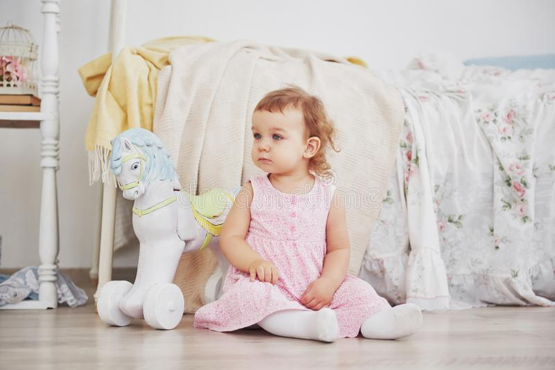 Beautiful little girl playing toys. Blue-eyed blonde. White chair. Children`s room. Happy small girl portrait. Childhood stock photography