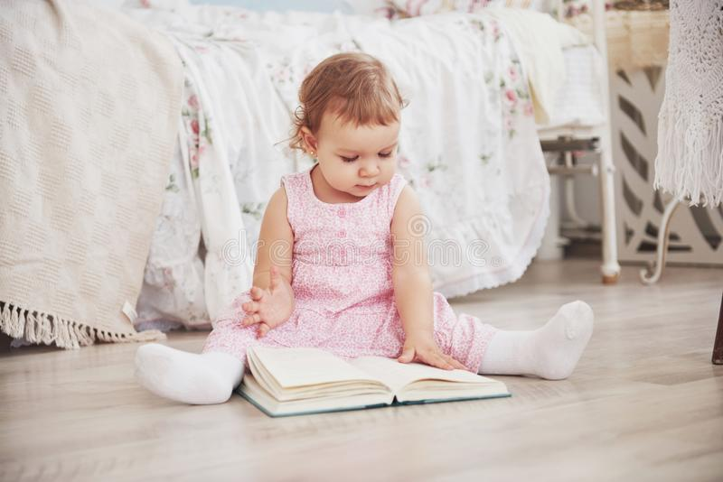 Beautiful little girl playing toys. Blue-eyed blonde. White chair. Children`s room. Happy small girl portrait. Childhood royalty free stock photo