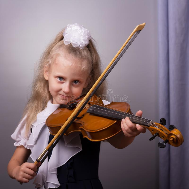 Beautiful little girl playing the violin on bright gray stock photo