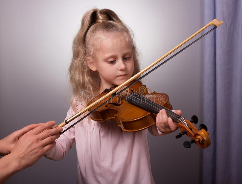 Beautiful little girl playing the violin on gray background royalty free stock photos