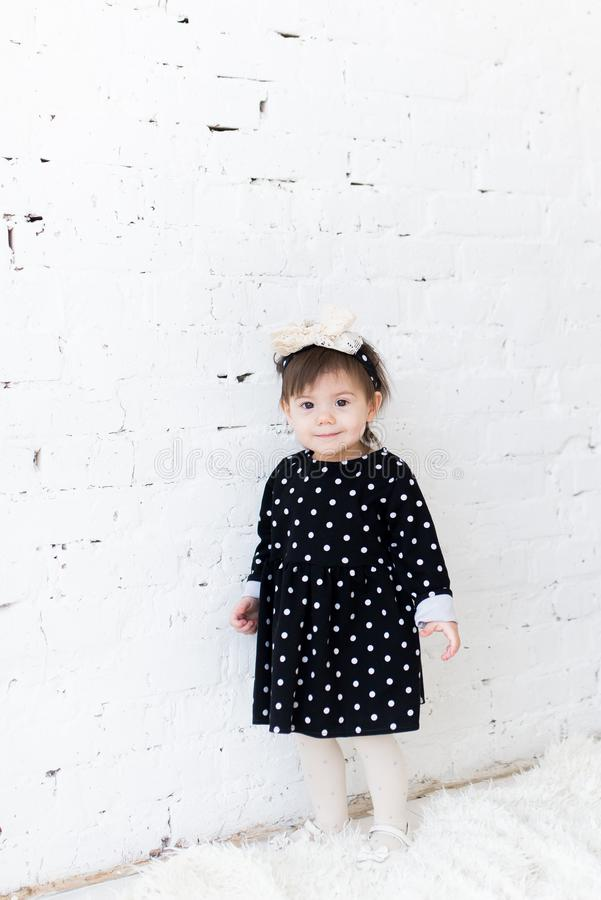Beautiful little girl in a polka dot dress is standing near the white brick wall and smiling. Birthday celebration, greetings, fun. Party for children stock photos