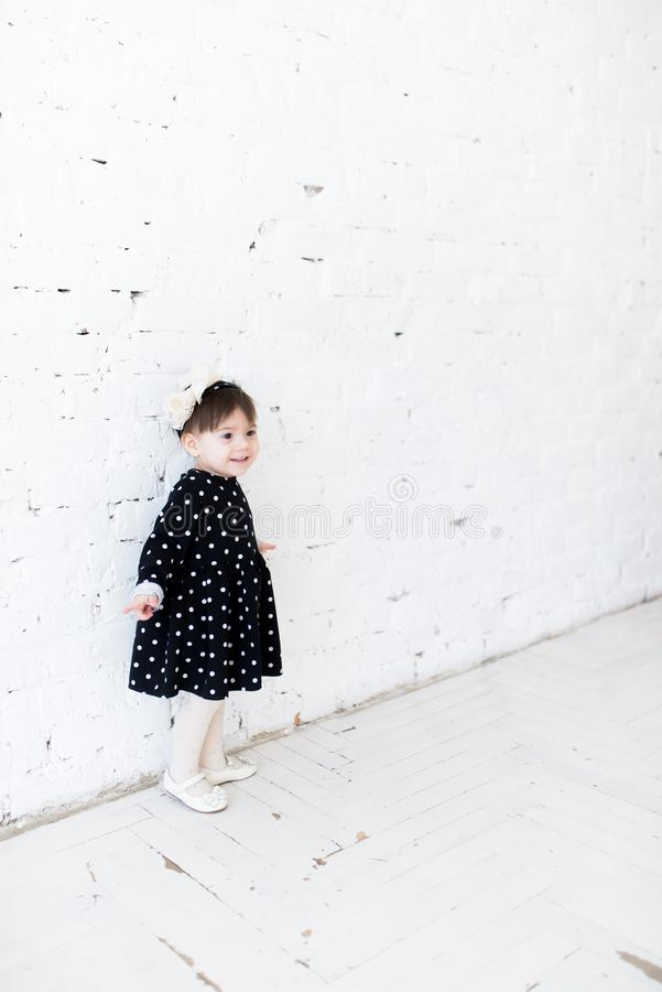 Beautiful little girl in a polka dot dress is standing near the white brick wall and smiling. Birthday celebration, greetings, fun. Party for children stock images