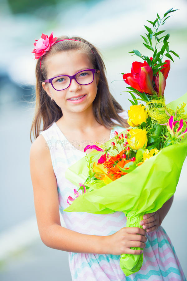 Beautiful little girl posing with a large bouquet of flowers. Girl with braces and glasses royalty free stock photo