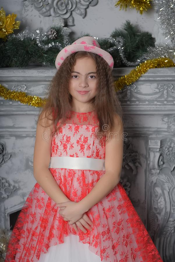 Beautiful little girl posing in red and white lace dress with a hat stock photos