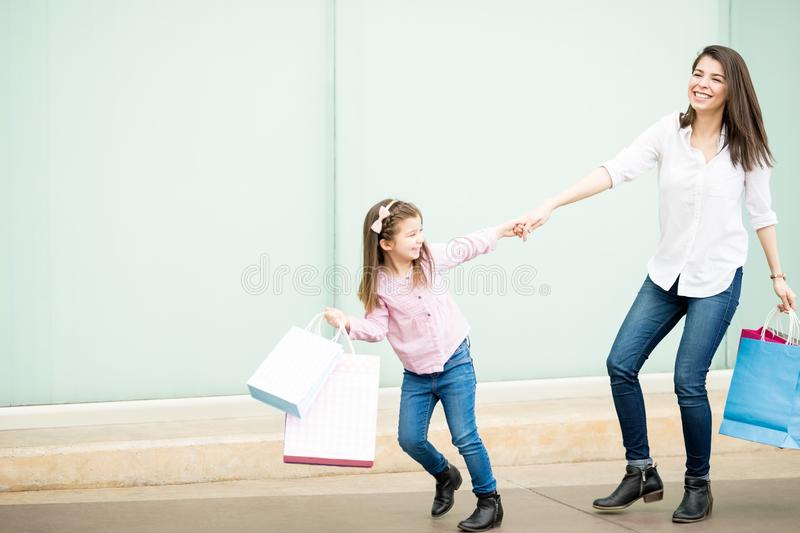 Beautiful little girl pulling mother outside shopping mall royalty free stock images