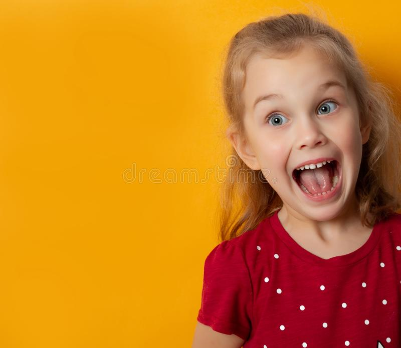 Beautiful little girl reacting emotionally screaming in shock stock image