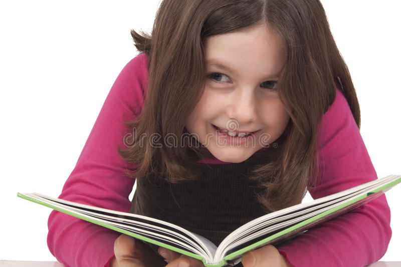 Beautiful little girl reading a book and smiling. Isolated on white stock photos