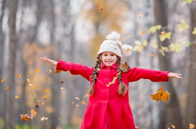 Beautiful little girl in red coat with autumn leaves outdoors in a park stock photos